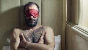 Mies istuu sängyllä side silmillä. Kuva elokuvasta Chevalier (2015).