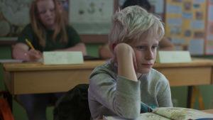 Sune sitter lutad över en skolbok vid sin pulpet i klassrummet.