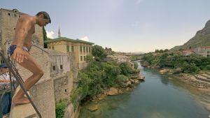 En ung man hoppar från Stari most i Mostar.