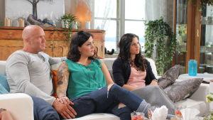 Tiina, hänen miehensä ja siskonsa katsovat kuvassa oikealle kuunnellen toimittaja Mapen puhetta.