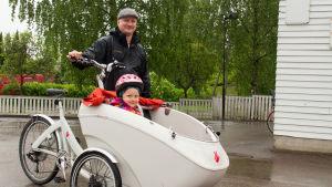 Vanhempi ja lapsi pyöräilemässä.