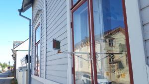 En så kallad skvallerspegel som sitter fast i väggen utanför ett fönster på ett trähus i stadsdelen Neristan i Karleby.