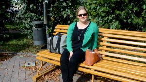 En kvinna som sitter på en gul parkbänk.