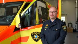 Akutvårdschef poserar framför en ambulans