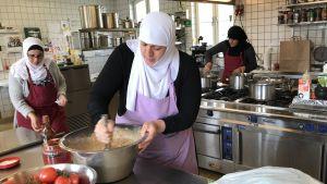 Tre kvinnor med huvudduk lagar mat i ett storkök.