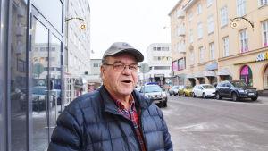 En medelålders man står i stadsmiljö. Han tittar in i kameran och håller på att säga något.