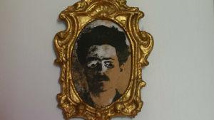 En liten guldtavla med guldram. Porträtt på en man i bruna nyanser. Manipulerat fotografi.