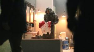 Mies tummassa suojapuvussa pitelee valkoista, punaiseksi värjäytynyttä kangasta. Edustalla kaksi tummaa hahmoa. Kuva on making of -kuva.