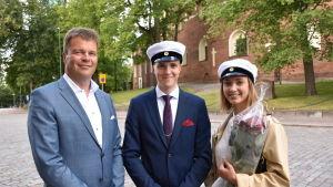 Far och son Österbacka och Irina Grön står utanför Akademihuset.