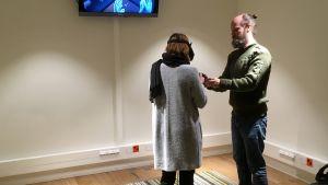 Joachim Högväg ger Milja Ångerman instruktioner om hur man rör sig i en virtuell värld.
