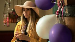 Närbild på Jenna (Linnea Skog) iklädd en stor damhatt och med ett dricksglas i handen.