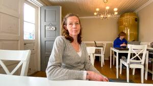 En kvinna som sitter vid ett bord.