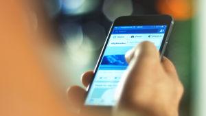 En person är inne i Facebook-applikationen på sin smarttelefon.