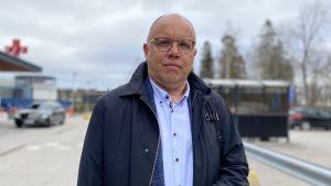 En man med glasögon och mörkblå ytterrock står utomhus och håller ett munskydd i ena handen och tittar in i kameran. I bakgrunden syns ingången till ett sjukhus.