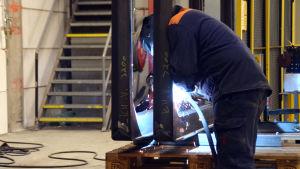 En person svetsar på ett föremål i en fabrikslokal.