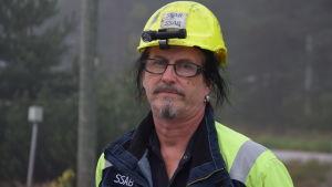 en man i blågula verkstadskläder,  och gul skyddshjälm. Utomhus, dimma, man kan parkeringsplats och lite skog i bakgrunden.