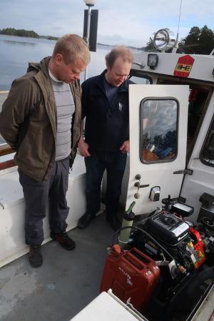 två män tittar på en vattenpump i släckningsbåten