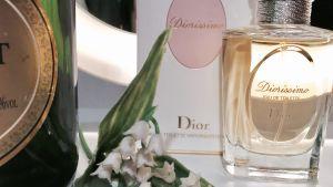 En flaska champagne, en parfymflaska av Dior och liljekonvaljer i plast.