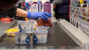 En kund med blåa skyddshandskar lyfter upp varor på ett kassaband. På kassabandet kan man se tomater, fil och yoghurt.