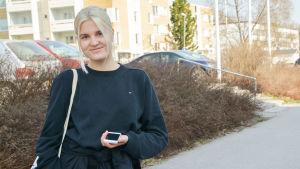 Kvinna klädd i svart poserar på gångväg