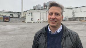 En man står på bakgården av en stor industribyggnad.