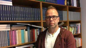 Jukka Lindqvist står framför bokhyllor.