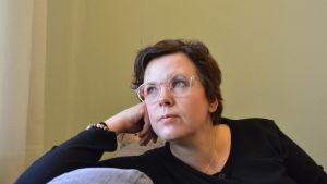 En kvinna i svart skjorta och med glasögon snett ut från ett fönster (som inte syns i bild).