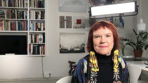 Rosa Liksom istuu sisätiloissa kuvattavana.