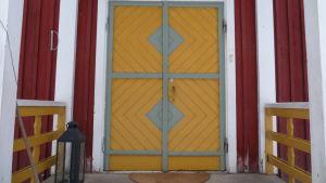 Närmare bild på en senapsgul, tvådelad ytterdörr till den gamla skolan i Tenala, numera Villa Christine.