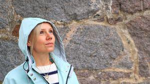 Malin Tverin står framför stenmur, tittar uppåt.