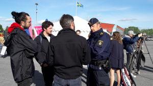 En polisman står och diskuterar med aktiva invånare i Järva.