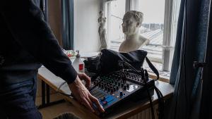 Byst på Runeberg och ett mixerbord.