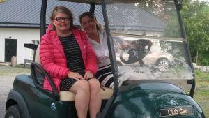Maria Pick och Annemari Andrésen sitter på en golfbil.