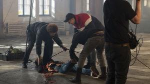 Viki ja Köpi nostavat lattialta testinukkea, jonka vatsanpäällä ollut vesimelooni on hajonnut.