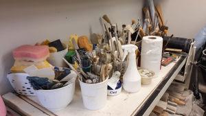 Burkar med penslar, svampar och andra redskap på ett diskbord.
