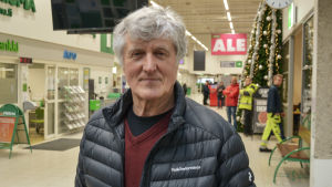 Man i grått hår med vinterjacka tittar in i kameran. Han står inne i butiksmiljö.