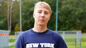 Andreas Isaksson står utomhus i t-shirt och tittar in i kameran.