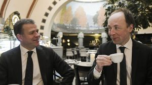 Petteri Orpo och Jussi Halla-aho dricker kaffe och ler mot varandra.