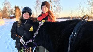 Irina Ala-Kopsala och Senja Meriläinen med kon Omena.