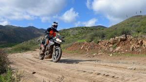Kristian Råstedt kör motorcykel på en sandväg.