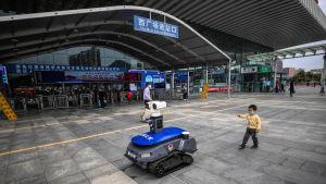 En polisrobot påminner människor om att de ska bära skyddsmask, och mäter febern på dem.  Shenzhen,  provinsen Guangdong 6.3.2020