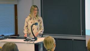 En kvinna står vid ett skrivbord med papper i handen. I ett klassrum.