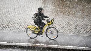 Nainen pyöräilee lumisateessa Helsingissä.