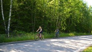 Kaarina Hurtta och Sari Siikala cyklar längs med Eriksnäsvägen. I bakgrunden grön skog.
