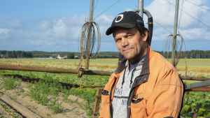 Jordbrukaren Christer Finne står på ett fält framför en bevattningsanläggning.