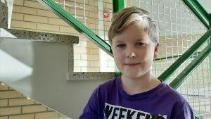 Elton Palmroos, en pojke med ljust hår och lila skjorta, står i en trappa med grönt räcka.