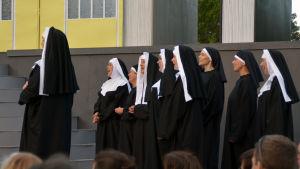 Nunnorna sjunger på scenen.