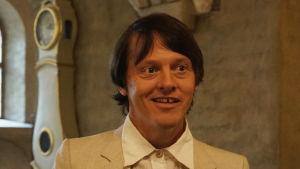 Thure Lindhardt som Nikolai Astrup i filmen Flammen over Jølster, som spelades in också i Åbo Domkyrka.