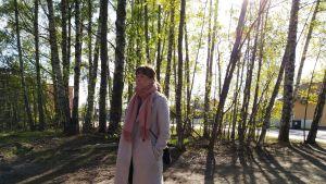 En kvinna som bor i Mosabacka står och lyssnar på en diskussion. Solen skiner mellan träden bakom henne.