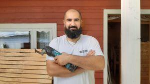 Man med ett sågverktyg i handen framför en rödmålad vägg.